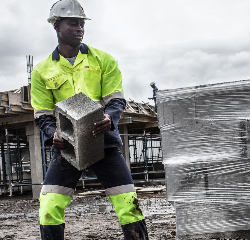 man wearing jonsson workwear jacket and pants, carrying a big and in construction